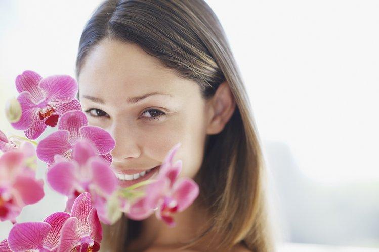 Bild des Gesichts einer Frau hinter einer Orchidee zur Darstellung von Gesichtsbehandlungen
