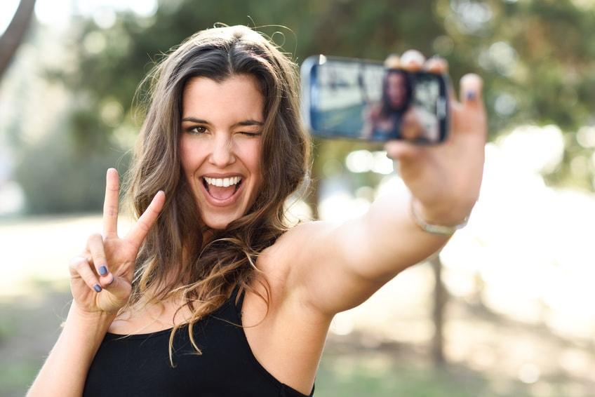 Frau, die ein Selfie mit ihrem Smartphone macht